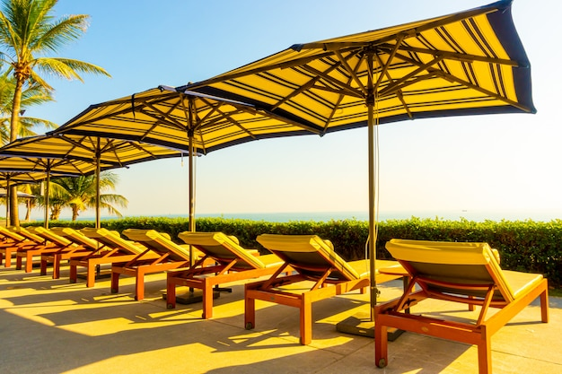 Beautiful luxury umbrella and chair around outdoor swimming pool in hotel and resort with coconut palm tree