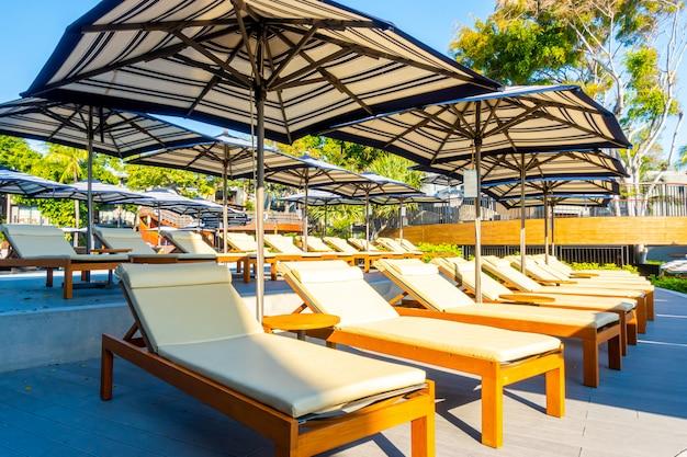 Красивые роскошные зонтики и стулья вокруг открытого бассейна в отеле
