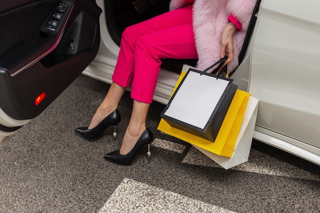 車の中でショップバッグとシックでファッショナブルな魅力的な衣装で美しい豪華な若い女性