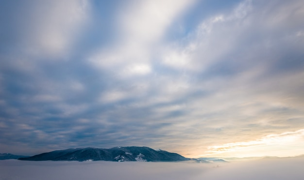 Прекрасные волшебные виды на горные вершины расположены между туманом и перистыми облаками.