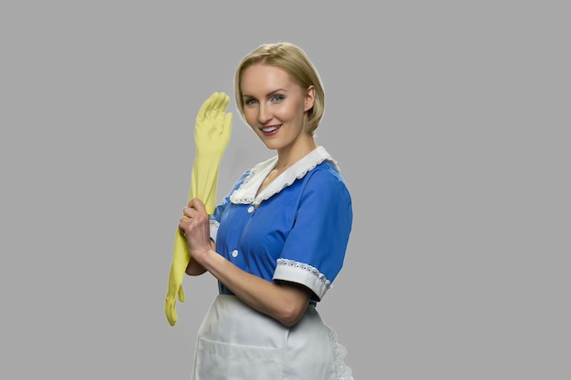 Beautiful maid with rubber gloves looking at camera. portrait of happy caucasian housemaid dressed in uniform posing againt gray background.