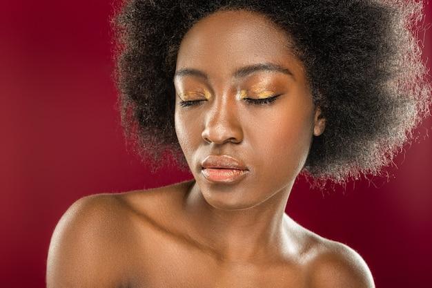 美しいメイク。美しい化粧をしながら目を閉じて立っている素敵な若い女性
