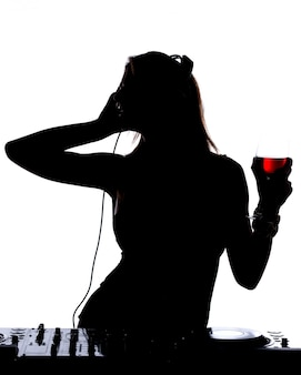 Beautiful male dj silhouette with is standing at her deck mixing sound.