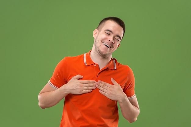 緑のスタジオの背景に分離された美しい男性の半身像。若い感情的な驚いた男