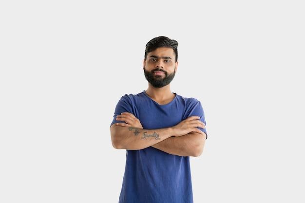 Красивый мужской поясной портрет, изолированные на белом фоне студии. молодой эмоциональный индус. выражение лица, человеческие эмоции, концепция рекламы. улыбается, уверенно стоит со скрещенными руками.