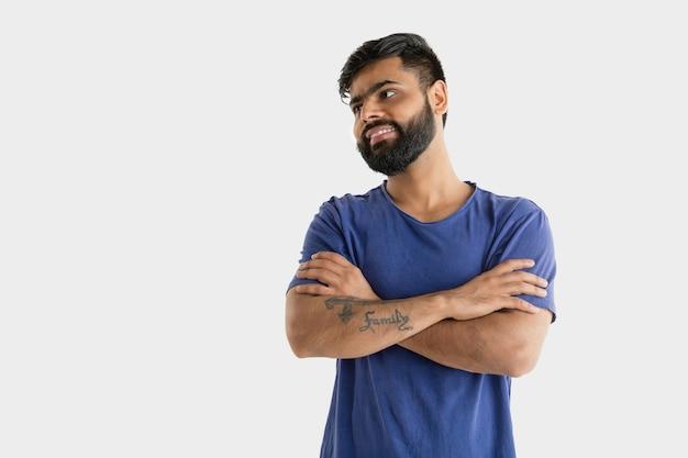 흰색 스튜디오 배경에 고립 된 아름 다운 남성 절반 길이 초상화. 젊은 정서적 힌두교 남자. 표정, 인간의 감정, 광고 개념. 웃고, 교차 손으로 자신감을 서.