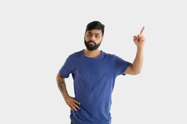 흰색 스튜디오 배경에 고립 된 아름 다운 남성 절반 길이 초상화. 블루 셔츠에 젊은 감정적 인 힌두교 남자. 표정, 인간의 감정, 광고 개념. 가리키고 선택합니다.