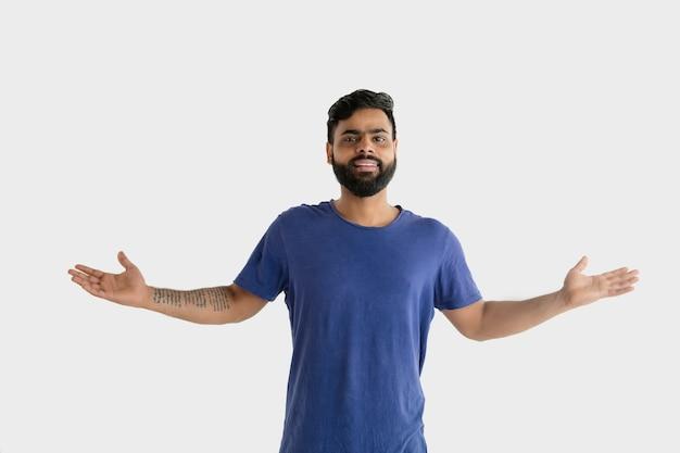 흰색 스튜디오 배경에 고립 된 아름 다운 남성 절반 길이 초상화. 블루 셔츠에 젊은 감정적 인 힌두교 남자. 표정, 인간의 감정, 광고 개념. 발표 및 초대.