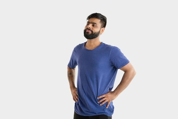 흰색 스튜디오 배경에 고립 된 아름 다운 남성 절반 길이 초상화. 블루 셔츠에 젊은 감정적 인 힌두교 남자. 표정, 인간의 감정, 광고 개념. 서서 웃고.