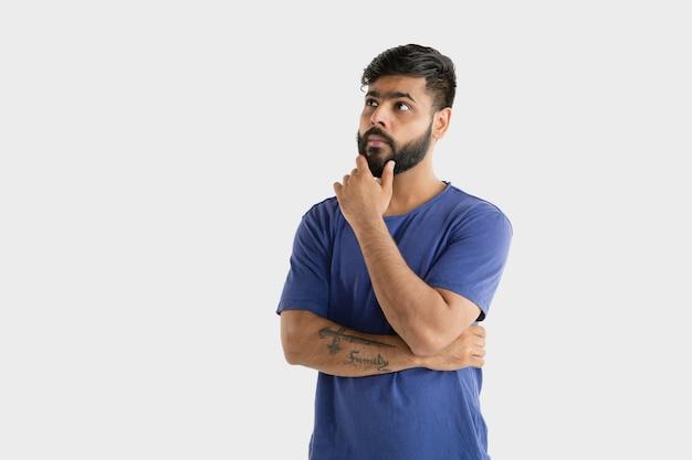 흰색 스튜디오 배경에 고립 된 아름 다운 남성 절반 길이 초상화. 블루 셔츠에 젊은 감정적 인 힌두교 남자. 표정, 인간의 감정, 광고 개념. 생각하거나 선택합니다.