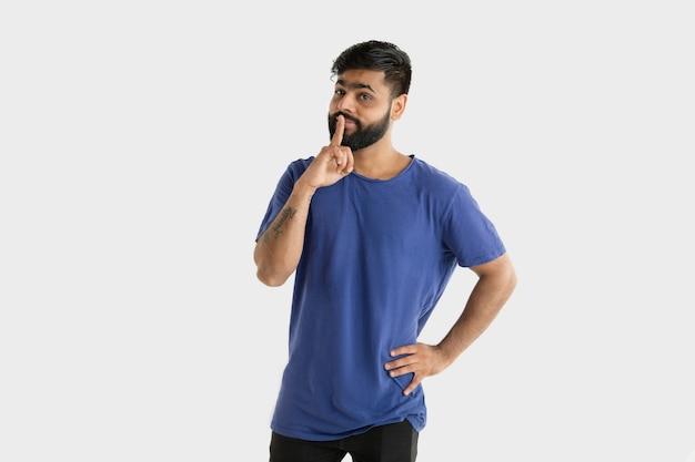 흰색 스튜디오 배경에 고립 된 아름 다운 남성 절반 길이 초상화. 블루 셔츠에 젊은 감정적 인 힌두교 남자. 표정, 인간의 감정, 광고 개념. 생각하고, 비밀을 속삭이는 것.