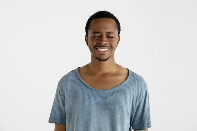白い壁に分離された美しい男性の半分の長さの肖像画。青いシャツを着た若い感情的なアフリカ系アメリカ人の男。顔の表情、人間の感情、広告のコンセプト。笑って、クレイジーハッピー。
