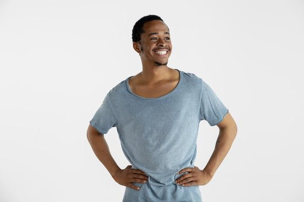 흰 벽에 고립 된 아름 다운 남성 절반 길이 초상화. 블루 셔츠에 젊은 감정적 인 아프리카 계 미국인 남자. 표정, 인간의 감정, 광고 개념. 서서 웃고.
