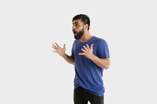 Красивый мужской поясной портрет изолированный на белой стене. молодой эмоциональный индус в голубой рубашке. выражение лица, человеческие эмоции, концепция рекламы. удивлен, шокирован, безумно счастлив.