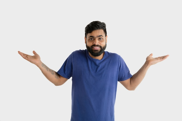 白い壁に分離された美しい男性の半分の長さの肖像画。青いシャツを着た若い感情的なヒンドゥー教の男。顔の表情、人間の感情、広告のコンセプト。プレゼンテーションと招待。