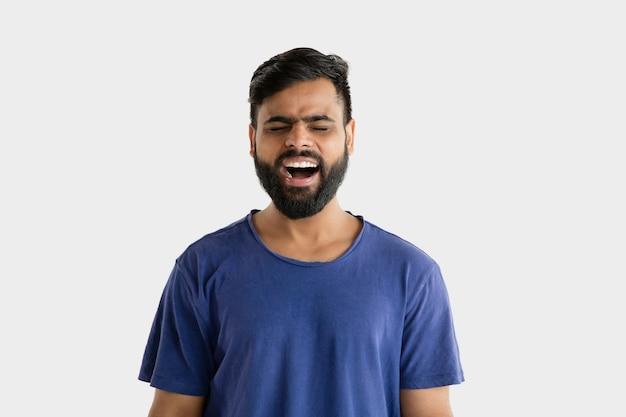 흰 벽에 고립 된 아름 다운 남성 절반 길이 초상화. 블루 셔츠에 젊은 감정적 인 힌두교 남자. 표정, 인간의 감정, 광고 개념. 비명을 지르거나 웃음.