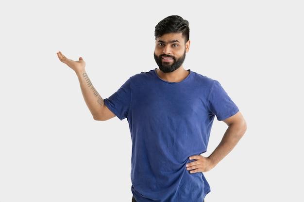 Красивый мужской поясной портрет изолированный на белой стене. молодой эмоциональный индус в голубой рубашке. выражение лица, человеческие эмоции, рекламная концепция. показывает пустой пробел.