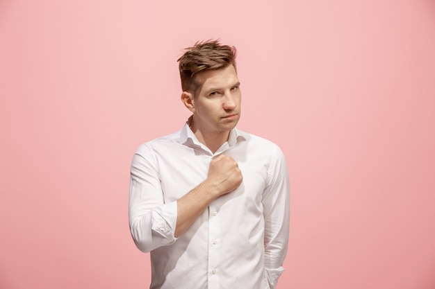 Beautiful male half-length portrait isolated on pink studio backgroud. the young emotional surprised man