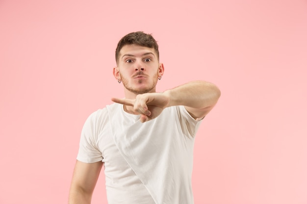 Beautiful male half-length portrait isolated on pink studio backgroud. the young emotional surprised