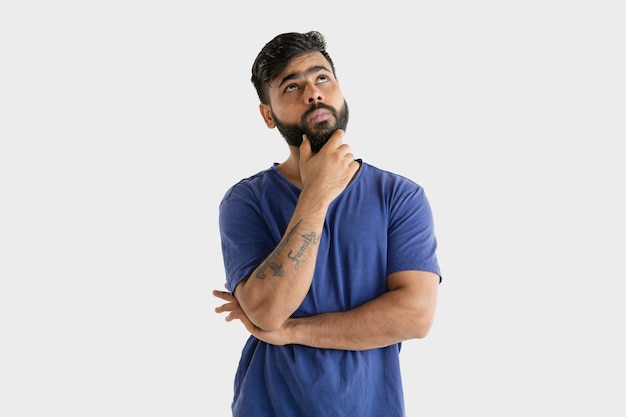 Beautiful male half-length portrait isolated on white studio background. young emotional hindu man in blue shirt. facial expression, human emotions, advertising concept. thinking or choosing.