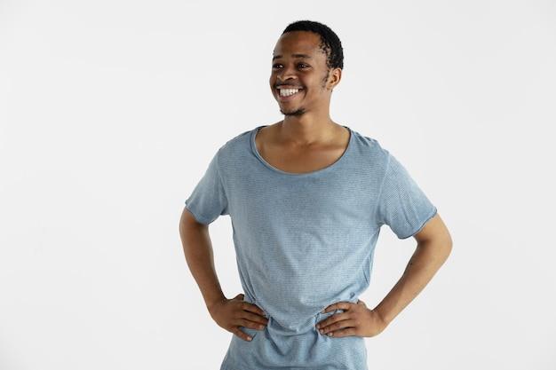 Bello ritratto a mezzo busto maschio isolato sulla parete bianca. giovane uomo afroamericano emotivo in camicia blu. espressione facciale, emozioni umane, concetto di annuncio. in piedi e sorridente.