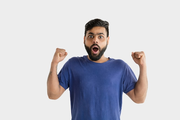Bellissimo ritratto maschio a mezzo busto isolato sul muro bianco. giovane uomo indù emotivo in camicia blu. espressione facciale, emozioni umane, concetto di annuncio. stupito, scioccato, follemente felice.
