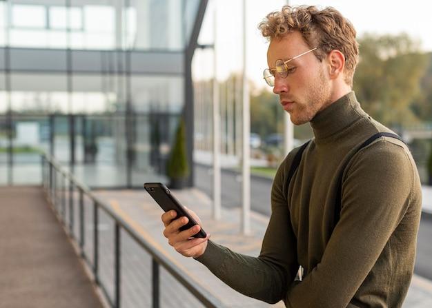 Красивая мужская модель просматривает свой телефон