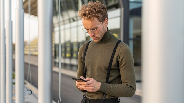 彼の携帯電話を見下ろす美しい男性モデル