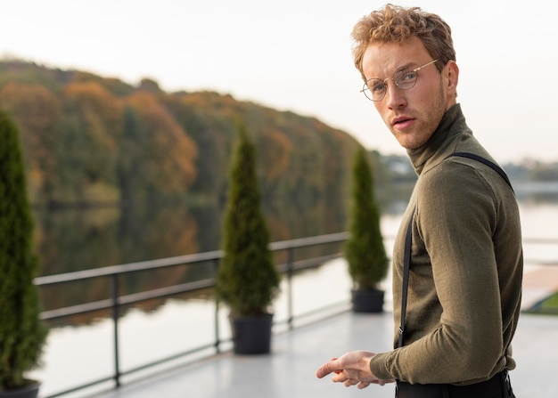호수 옆에 서있는 아름 다운 남성 모델