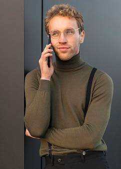 Bello modello maschio che comunica sul telefono all'aperto
