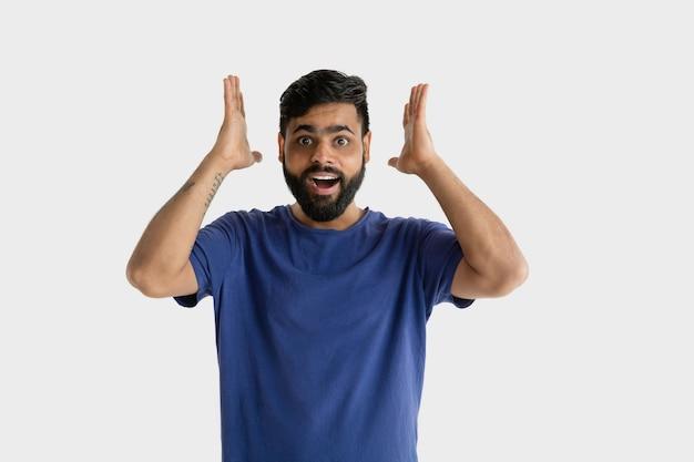 Bellissimo ritratto maschile isolato. giovane uomo indù emotivo in camicia blu. stupito, scioccato, follemente felice.