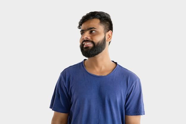 Bellissimo ritratto maschile isolato. giovane uomo indù emotivo in camicia blu. espressione facciale, emozioni umane. in piedi e sorridente.