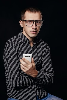 黒のシャツの縞模様の白い点で黒の背景に美しい男性の肖像画。ビジネスマン、成功した男、携帯電話を手に眼鏡をかけた若い男