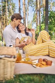 아름다운 남자와 맛있는 식사와 함께 정원에서 피크닉에서 편안한 웃는 여자