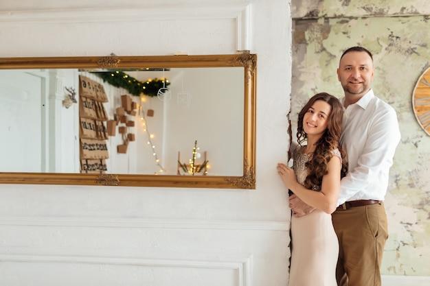 美しい男と女がクリスマスを祝っています。愛するカップルは大晦日にお互いを楽しんでいます
