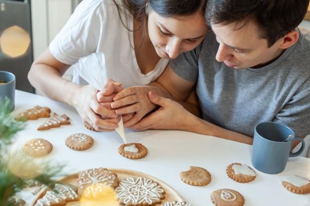 Красивые мужчина и женщина украшают рождественские имбирные пряники, два человека рисуют сердечко на стильном печеньке ...