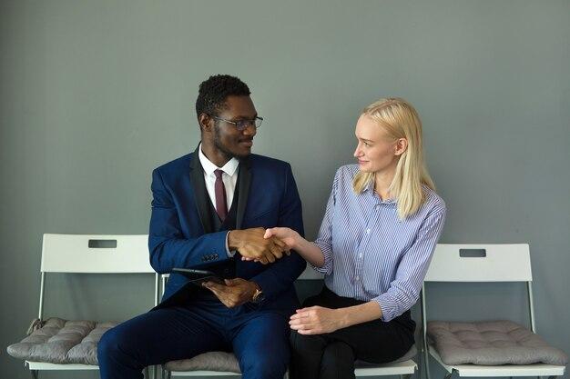 악수와 함께 의자에 사무실에서 아름다운 남자와 여자