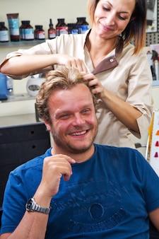 그의 머리카락을 건조하는 미용사 타격에 아름 다운 남자