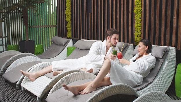 Beautiful man and a beautiful woman are relaxing in the spa drinking non -alcoholic cocktails