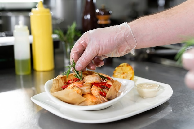 Beautiful man chef preparing dish with shrimps at table in kitchen