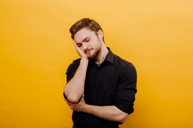 Beautiful man dreams tilting head on his hand, isolated yellow background,