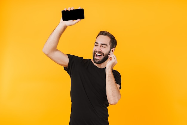 Beautiful man in earpods dancing and listening to music with cellphone isolated over yellow wall