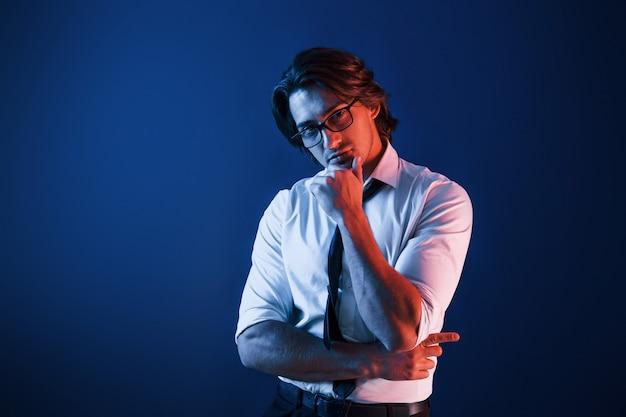 フォーマルな服装とメガネをかけた美しい男が、青いネオンの照明を備えたスタジオにいます。