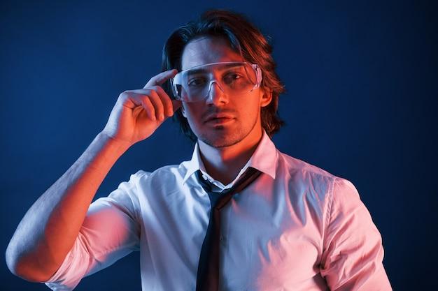 眼鏡をかけ、スーツとネクタイを着た美しい男が、青いネオンの照明のあるスタジオにいます。