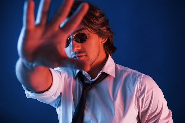 眼鏡をかけた美しい男がスタジオにいて、青いネオンの照明が彼の前に手を握っています。