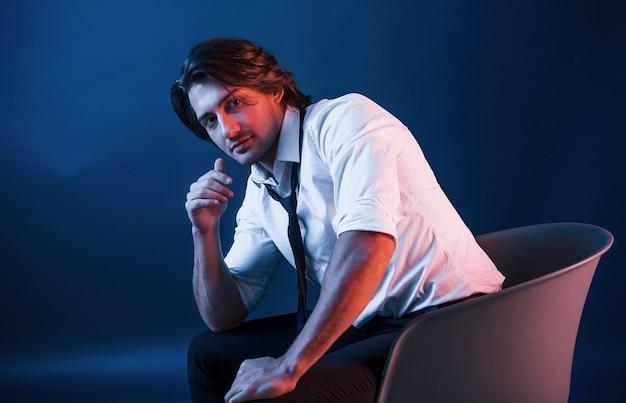 眼鏡をかけた美しい男が、青いネオンの照明でスタジオに座っています。