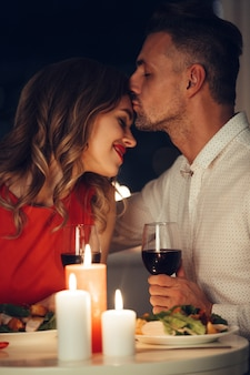 Beautiful man kissing his smiling happy lady while have romantic dinner