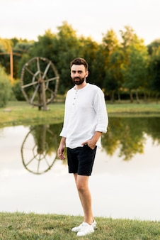 Красивый мужчина на фоне озера на улице в солнечный день