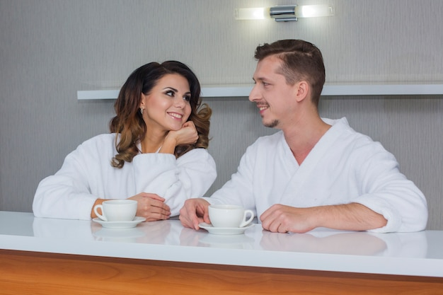 Beautiful man and sexy girl in white bathrobes chill together in morning