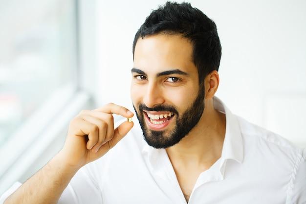 美しい男は薬、薬を服用します。ビタミンとサプリメント